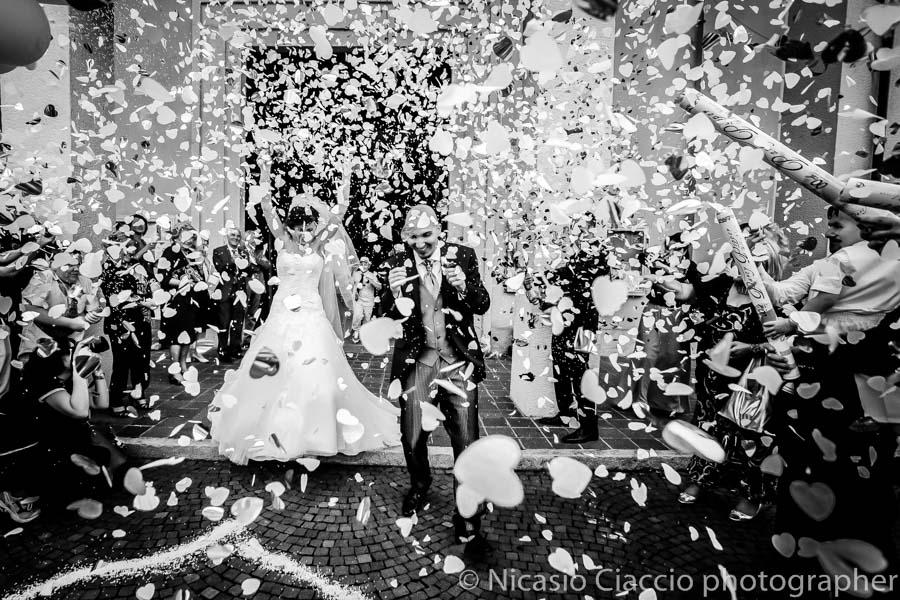 fotografia di sposi che escono dalla chiesa con coriandoli Come scegliere il fotografo del matrimonio può rivelarsi più complicato di quanto si pensi.