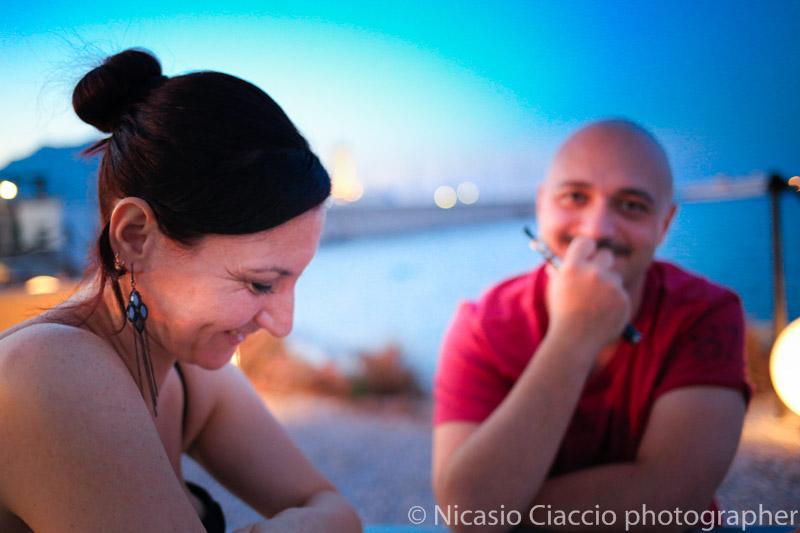Ritratto di Francesca e Vittorio all'imbrunire sulla cala di palermo. splendidi colori pastello del cielo che si riflette sul mare.
