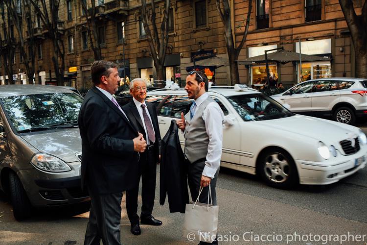 Lo sposo aspetta il tram mentre passa il taxi della sposa -foto matrimonio milano officine del volo-2