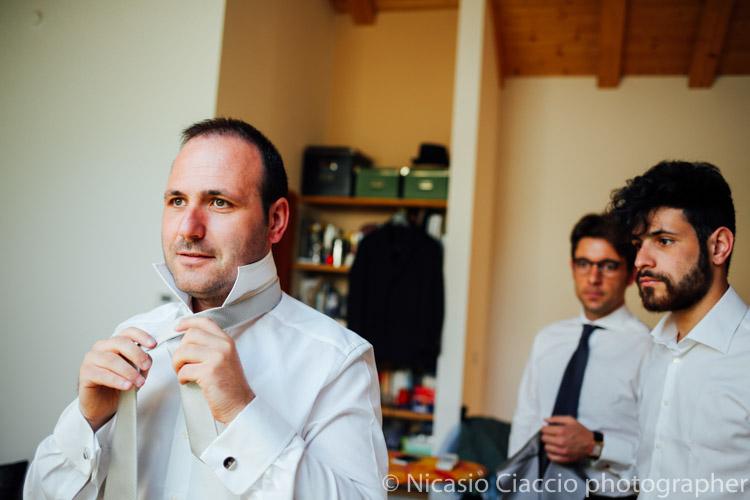Lo sposo intento a fare il nodo alla cravatta